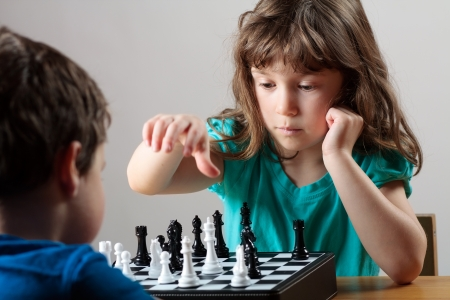 Cute little girl playing chess photo