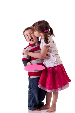Cute little girl kissing a boy holding a pink heart