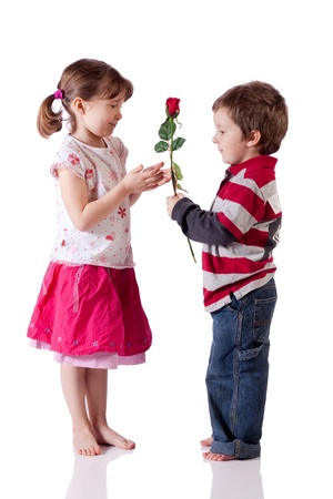 Cute little boy giving a rose to a girl photo