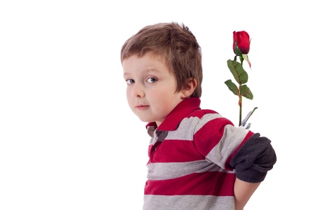 Cute little boy holding a red rose behind his back
