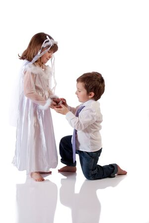 Cute little boy giving an engagement ring to a girl Stock Photo - 18576879