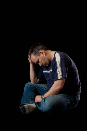 Depressed man on black background Stock Photo