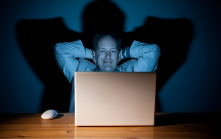 Man looking content in front of his computer Stock Photo - 18576857