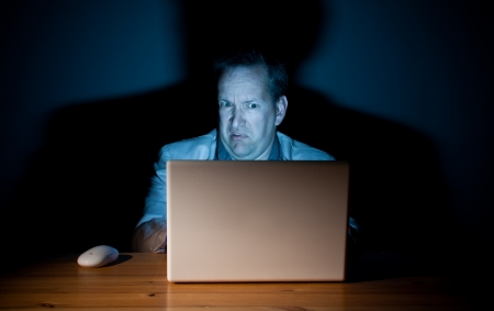 disgusted: Man looking disgusted in front of his computer