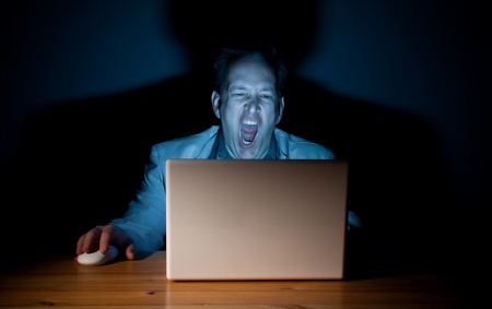 Man yawning in front of his computer