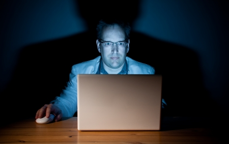 Man working late in front of his computer Stock Photo