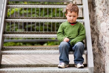 Sad little boy sitting alone on stairs