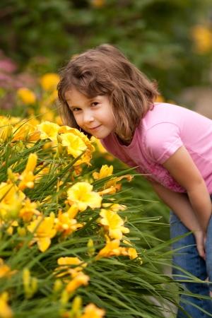 Cute little boy smelling yellow flowers