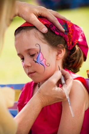 'face painting': Cute little girl getting make-up on her face Stock Photo