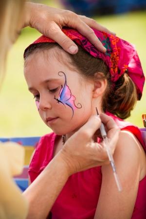 maquillaje infantil: Niña linda que consigue el maquillaje en su cara Foto de archivo