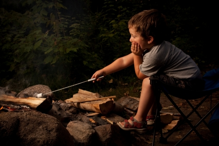 밤에 모닥불에 마시멜로를 요리하는 어린 소년
