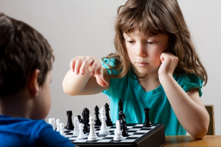 Cute little girl and boy playing chess together