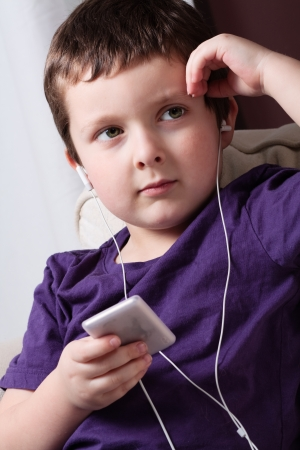 Cute little boy listening to music on a mp3 player photo