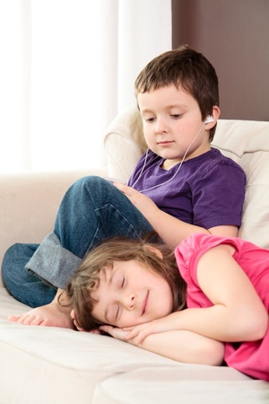 Boy listening to music on a mp3 player while his sister take a nap Stock Photo - 18577011