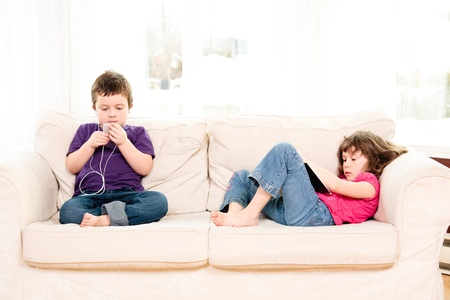 Boy listening to music and girl reading on a couch 스톡 콘텐츠