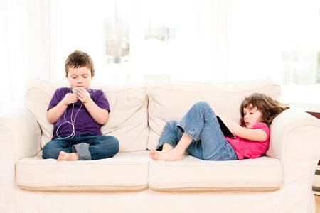 소파: 소년 소파에 음악과 소녀 읽기 듣기 스톡 사진