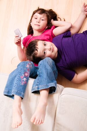 Girl listening to music while her brother is laying his head on her photo