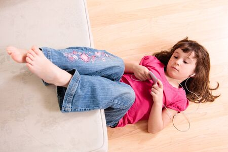 Girl listening to music while  laying on the floor Stock Photo - 18576977