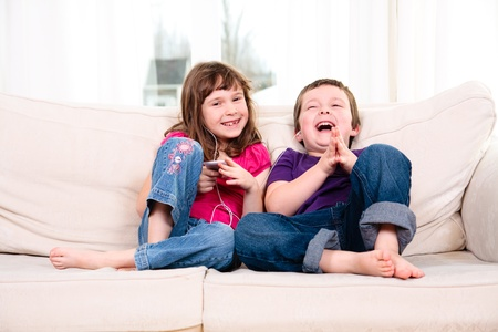 Children listening to music while sitting on a couch Stock Photo