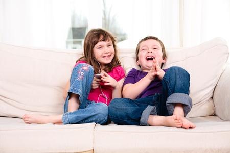 Kinderen luisteren naar muziek terwijl het zitten op een bank Stockfoto