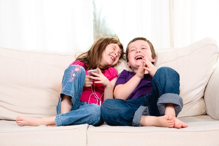 little girl smiling: Children listening to music while sitting on a couch Stock Photo