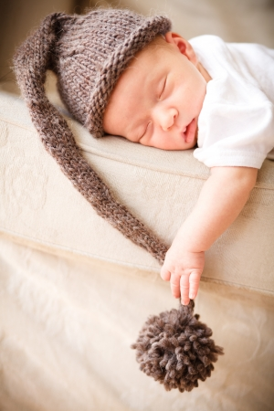 Newborn baby boy resting on a couch Stock Photo