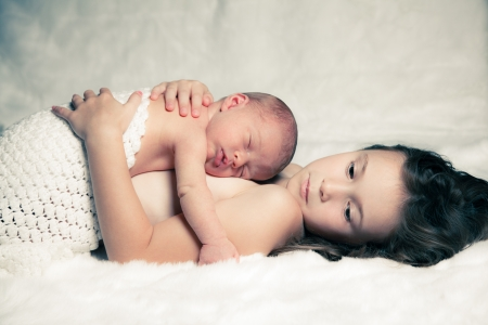 Newborn baby boy resting on his sister photo