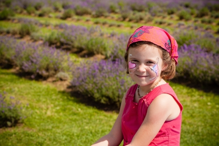 Cute little girl with make-up in a lavender field