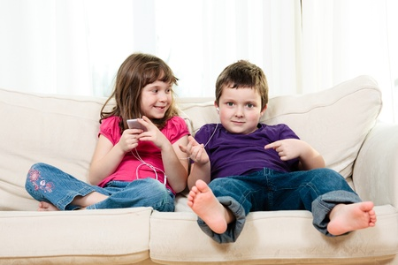Children listening to music while sitting on a couch photo