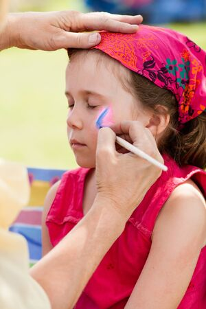 children painting: Cute little girl getting make-up on her face Stock Photo