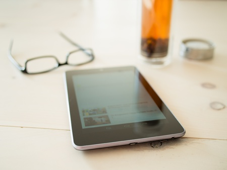 Seven inch tablet, tea and glasses on a rustic table