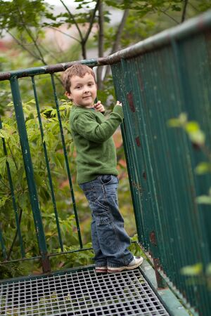 young boy smiling: Young boy smiling by a metal fence