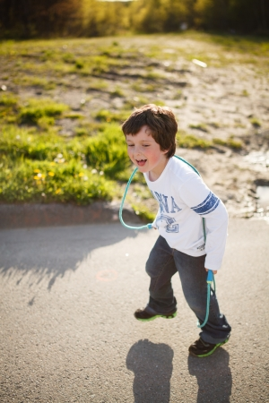 Cute little boy playing jump rope Stock Photo