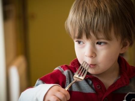 Baby boy eating with a fork in a restaurant Stock Photo