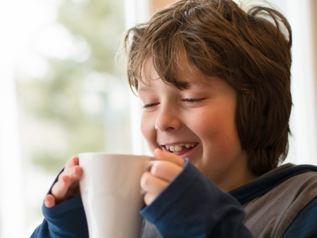 Young boy drinking a hot chocolate