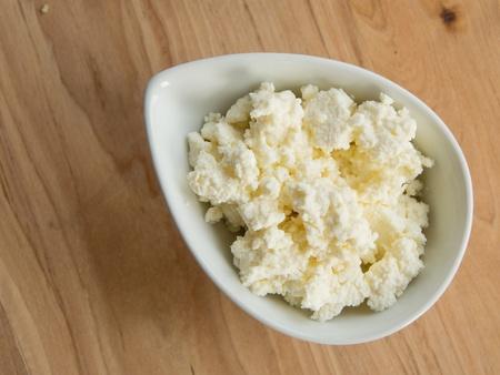 Zelfgemaakte kaas in een kom op een snijplank Stockfoto