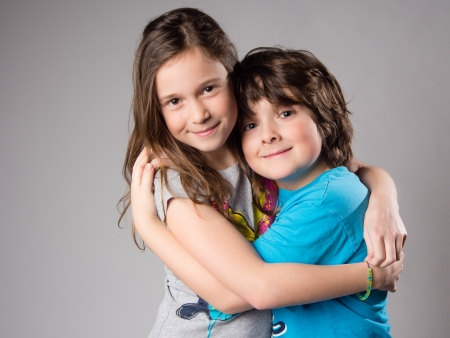 Brother and sister hugging in studio