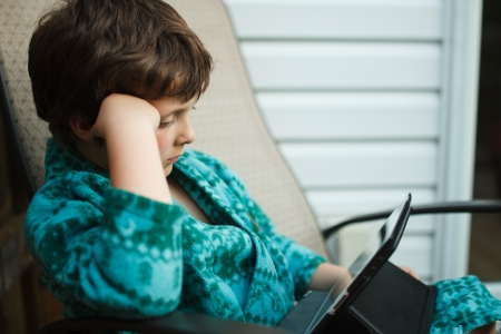 Boy reading on a tablet outside in pajamas