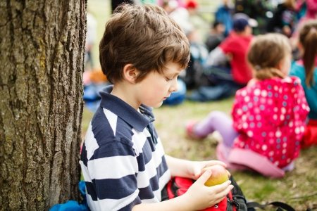 Boy sitting by a tree eating an apple on a school trip Stock Photo