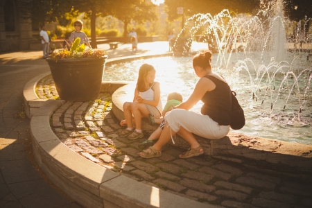 Family sitting by a fountain in downtown Montreal at sunset Stock Photo