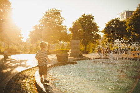 Boy standing by a fountain at sunset and getting wet