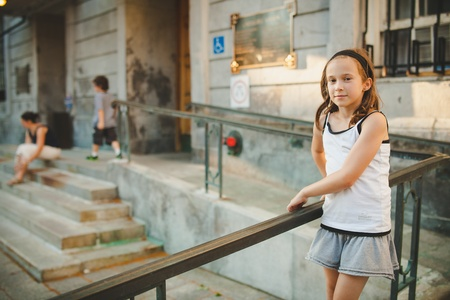 Girl standing outside while her brother is running around Banco de Imagens