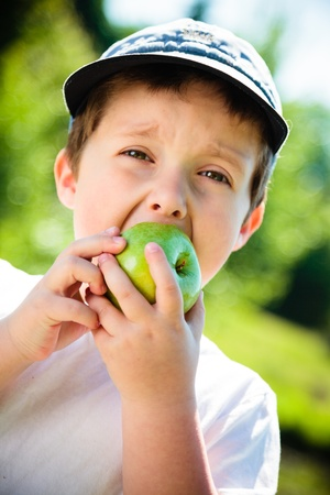 Boy eating a green apple photo