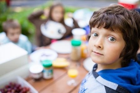 キャンプの朝食を待っている少年