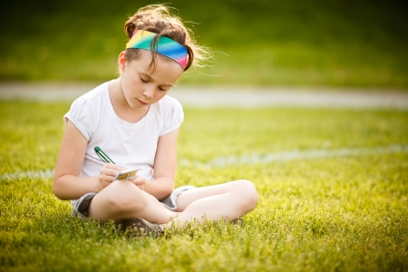 Little girl writing outside on the grass at the golden hour Stock Photo
