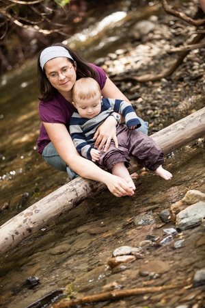 river trunk: Mother and son playing on a tree trunk in a river