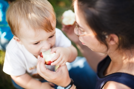 Mother helping her baby eat an apple