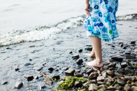 young girl feet: Girl walking in shallow water in a lake