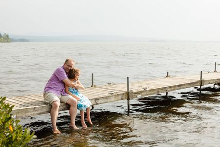 Father and daughter hugging on a wharf by a warm summer day photo