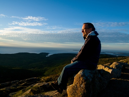 Man watching the sunrise over the sea on top of Cadillac Mountain in Acadia National Park photo
